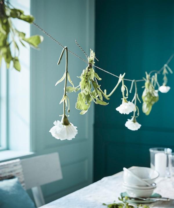 Appendi un nastro sopra la tavola e decoralo con dei fiori. Da IKEA trovi il nastro GIVANDE, disponibile in nero, nero/beige e bianco.