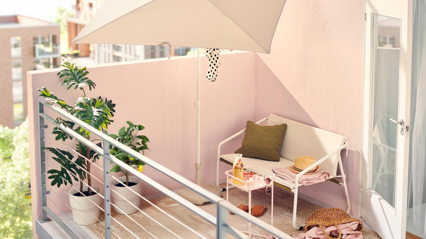 Après-midi ensoleillé sur un balcon urbain aménagé avec du mobilier d'extérieur blanc, dont un canapé deux places et un parasol.