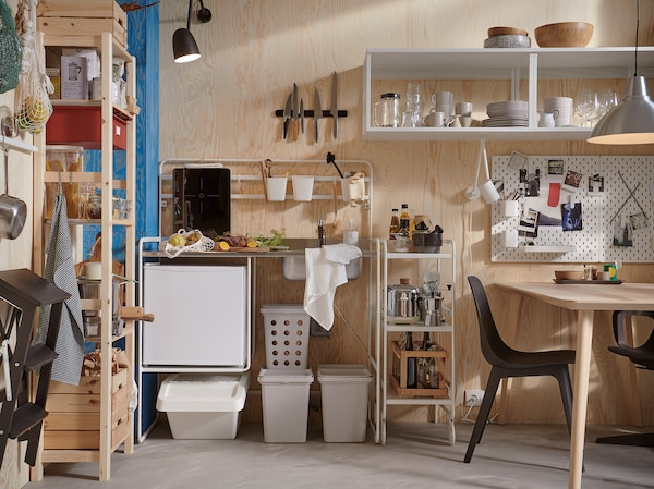 Apró és világos SUNNERSTA mini konyha, szürke szelektív hulladékgyűjtők, fenyő tárolórendszer és fekete székek.