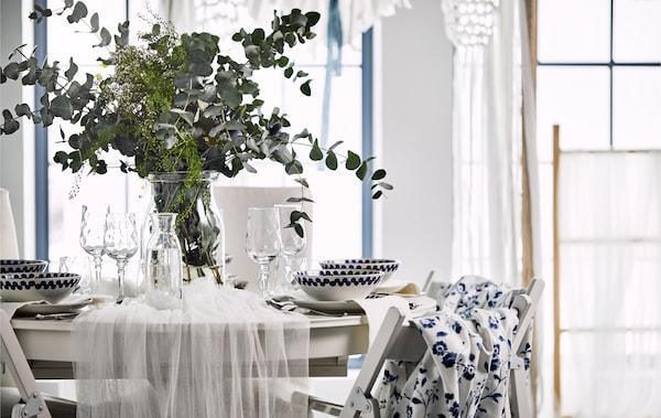 Aranjament de masă romantic, cu tul în jurul mesei și o vază cu flori sălbatice și frunze de eucalipt.