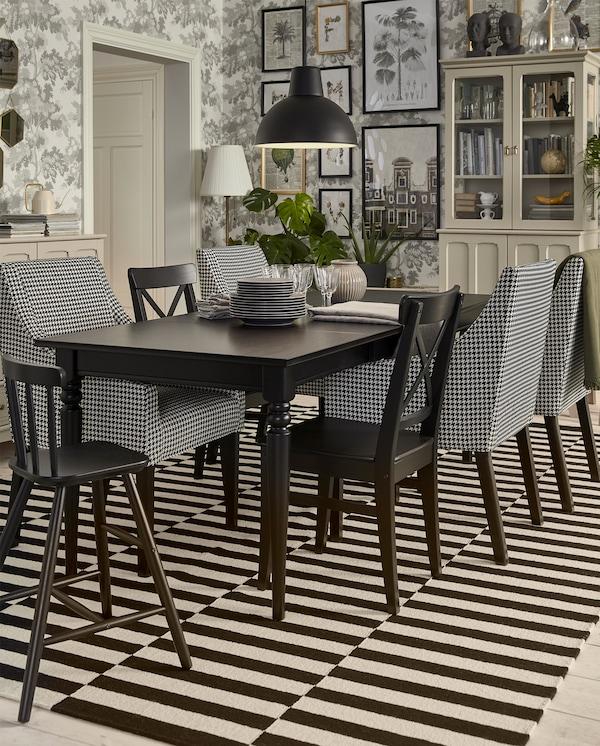أربعة كراسي بنمط مربعات مع مساند للذراعين، وكرسيان بلون أسود وكرسي أطفال أسود بجانب طاولة ممددة.