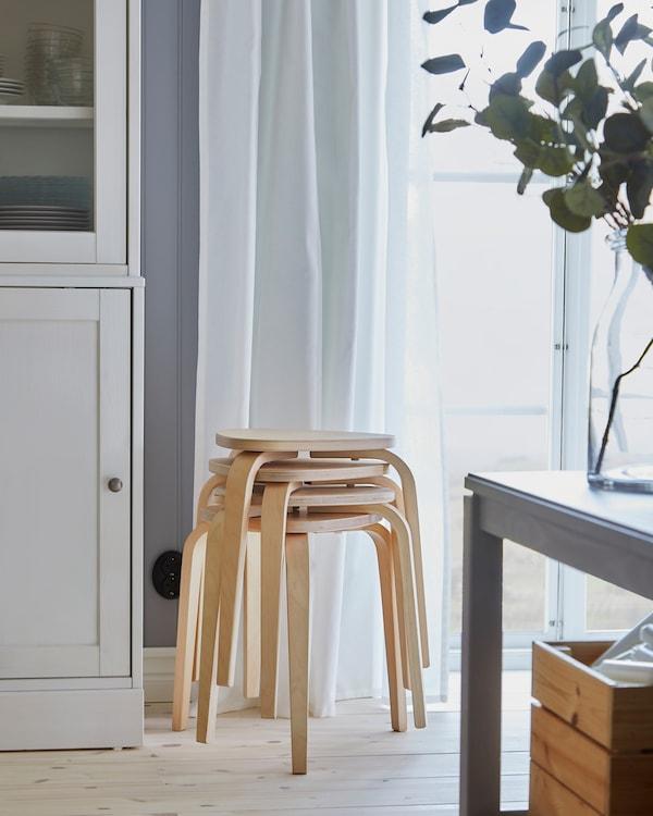 أربعة مقاعد KYRRE من خشب البتولا مكدسة بجانب نافذة، وتُستخد لتوفير مزيد من المقاعد بجانب طاولة الطعام عند تمديدها.