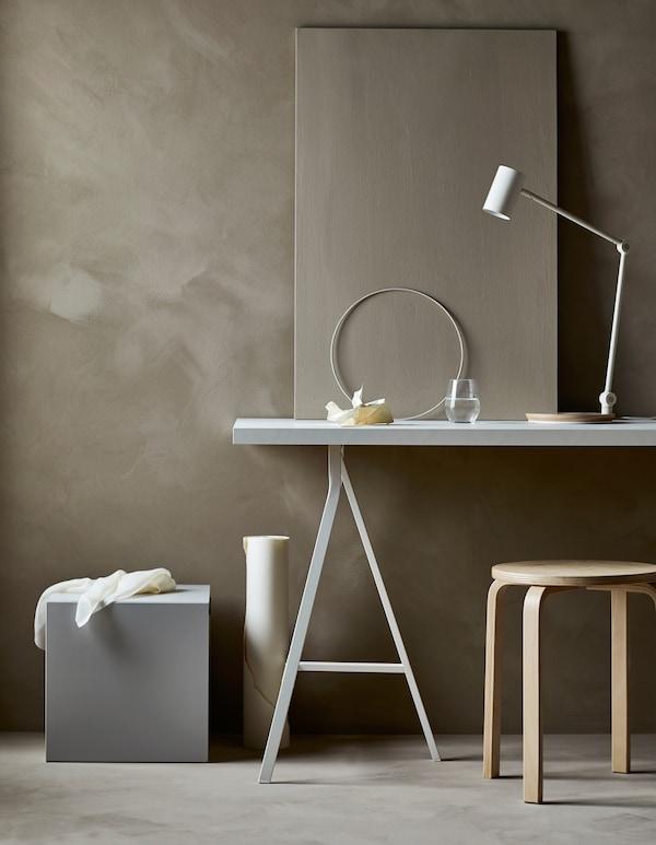 Arbejdsplads i minimalistisk stue med skrivebord, stol og udstyr skjult i opbevaring