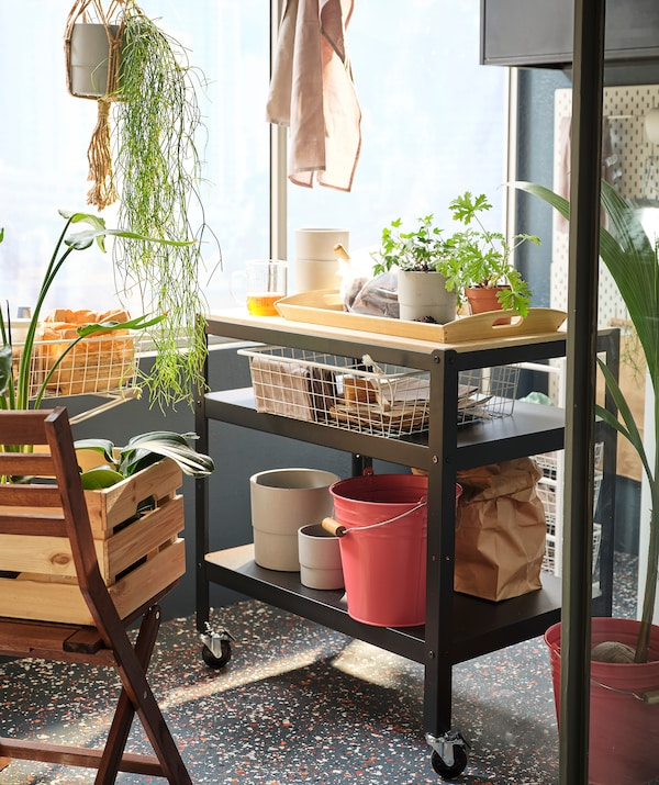 عربة بعجلات مع مساحة تخزين واسعة مليئة بنباتات وإكسسوارات الحدائق موضوعة على شرفة مضاءة بأشعة الشمس.