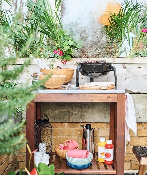 عربة خشبيةفي مساحةطهي خارجيةمع شواية على سطح عمل معدن وأوانيطعام وتوابل على رف من أعلى.