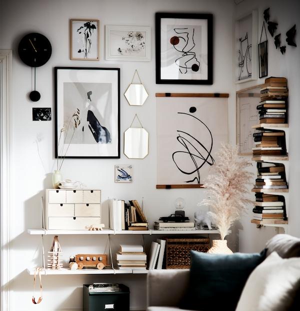 Área de uma sala de estar com livros em segunda mão, destaques em materiais naturais e uma galeria de arte em branco, preto e bege.