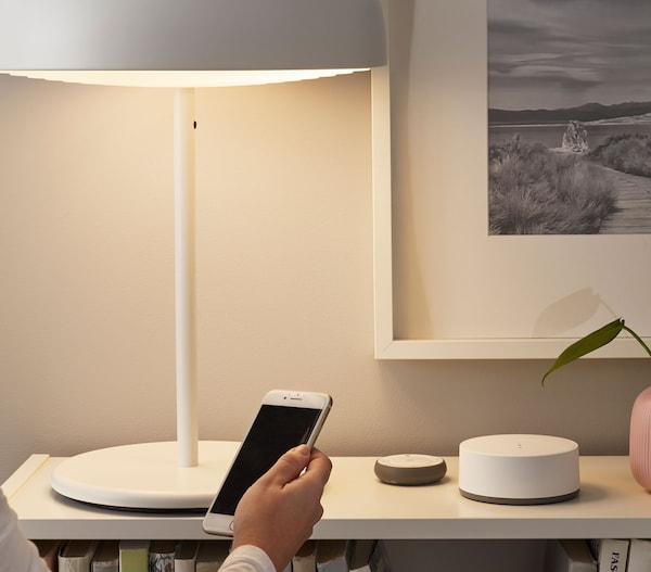 Arm holding a phone in front of a white book shelf with a wifi hub and lighting remote on it