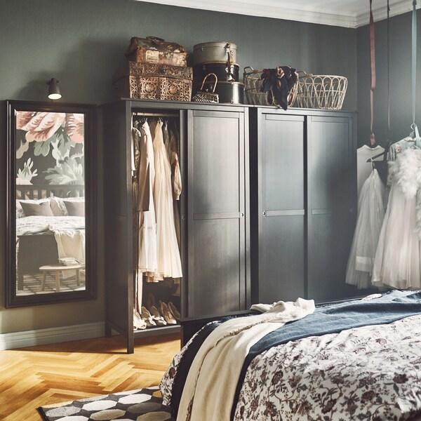 Armario abierto de pino HEMNES de tinte negro con puertas correderas para ver la ropa.
