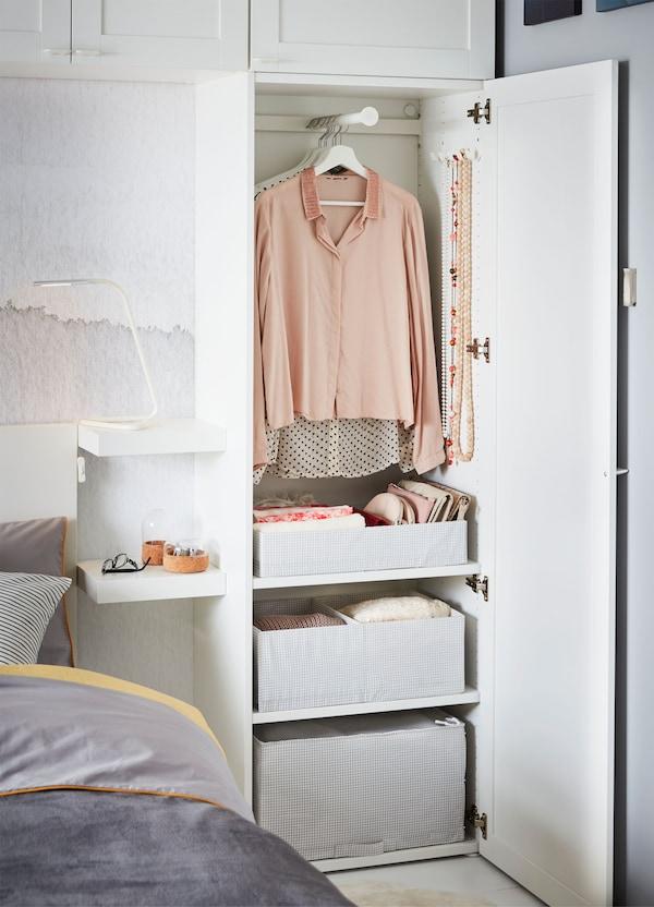 Armario blanco IKEA PLATSA abierto, junto a una cama, con ropa y cajas de almacenaje estampadas en el interior.