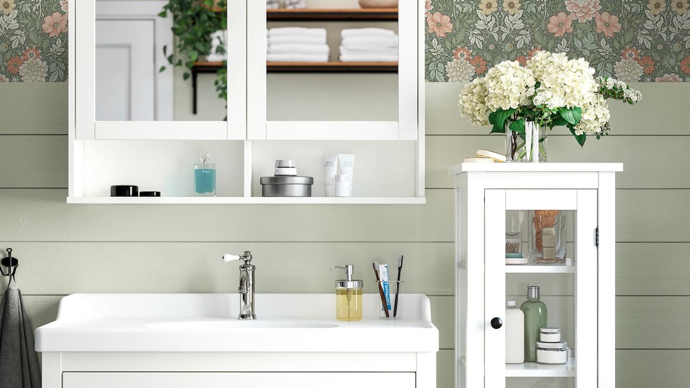 Armário com espelho HEMNES em branco, por cima de um armário com lavatório branco e ao lado de um armário alto com uma porta de vidro.
