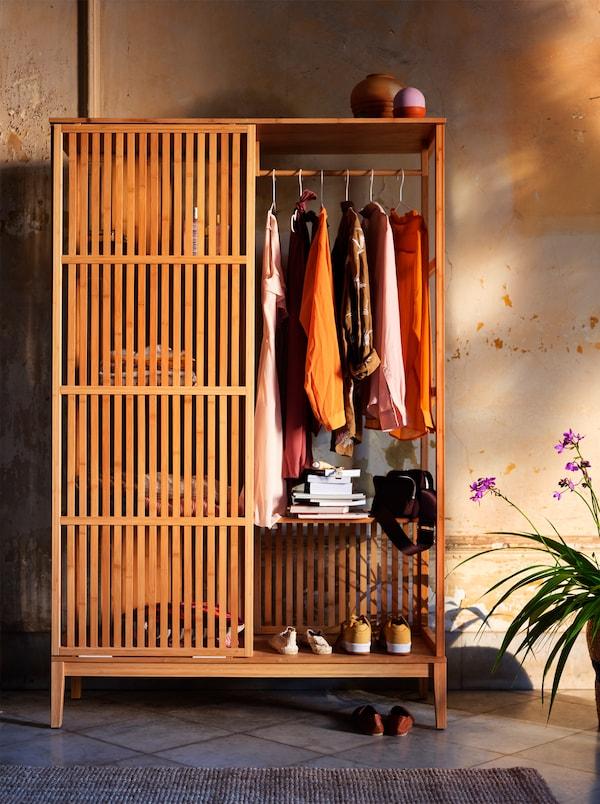 Armario de madera abierto con puertas correderas lleno de ropa de colores otoñales, contra una pared en amarillo anaranjado.