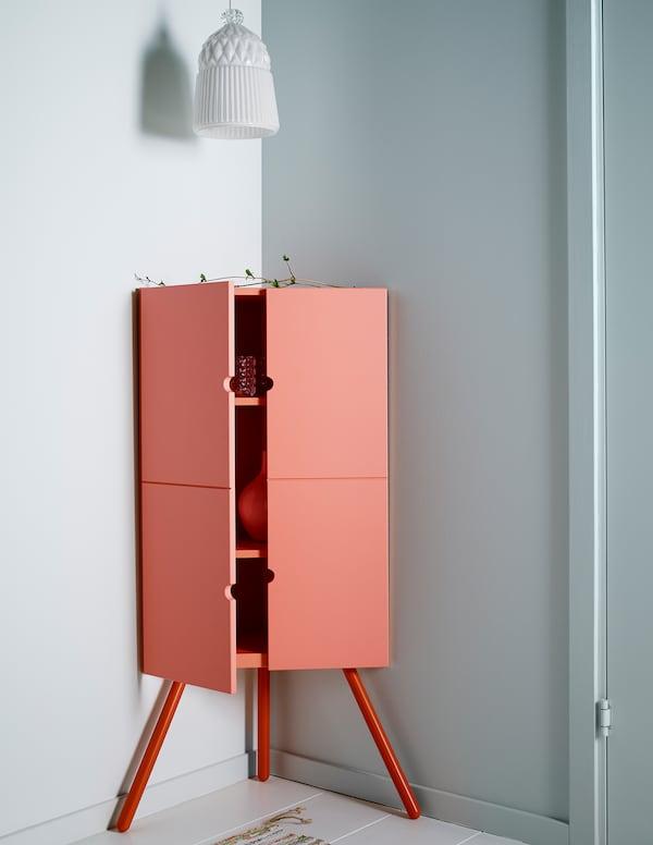 Armario esquinero de IKEA de madera en color rosa con una pantalla de lámpara de vidrio blanca colgada encima.