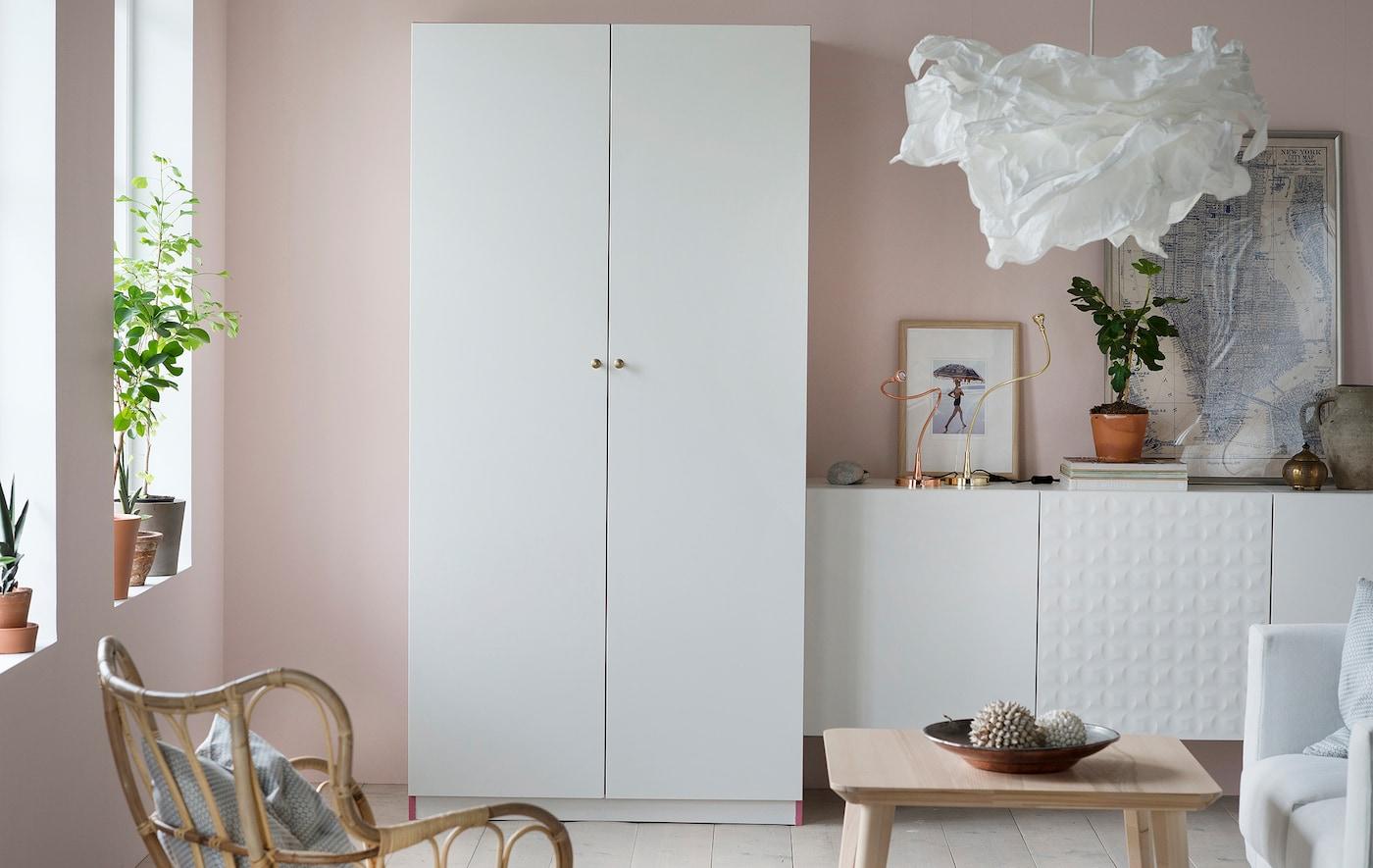 Armario PAX blanco en un amplio salón, con sus dos puertas blancas cerradas para que la habitación resulte apacible y acogedora.