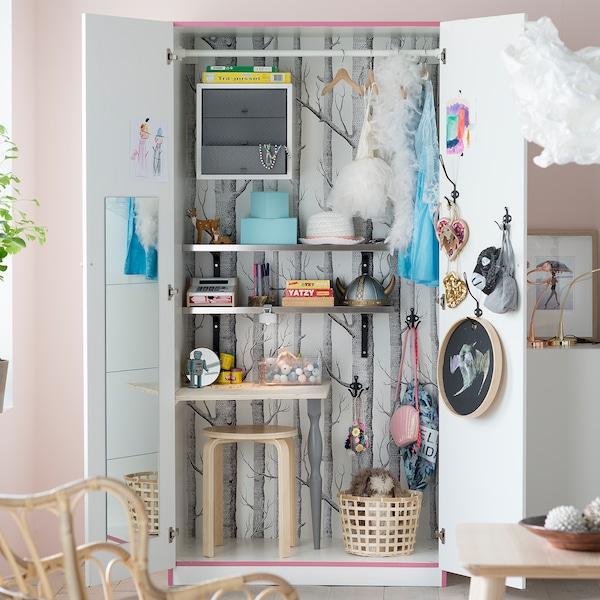 Armario PAX de IKEA en blanco convertido en zona de almacenaje de juguetes con estanterías, cesto y taburete en su interior.
