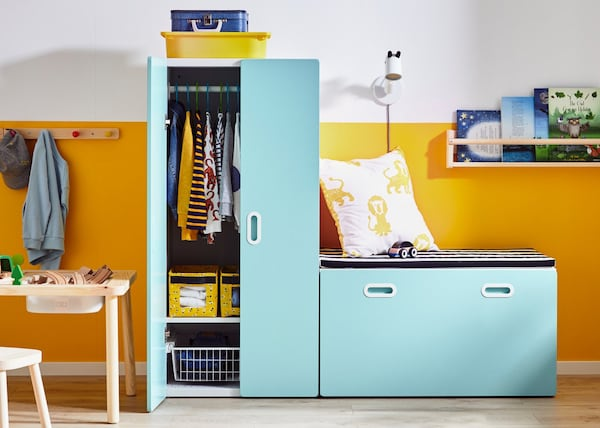 Armário STUVA com frentes azuis num quarto de criança amarelo e branco