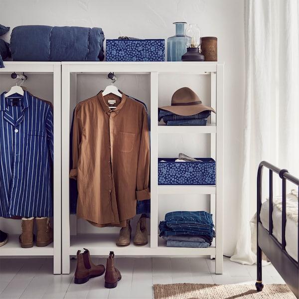 Armarios abiertos de madera maciza con tinte blanco IKEA HEMNES, llenos con ropa azul y marrón, gorros y zapatos.