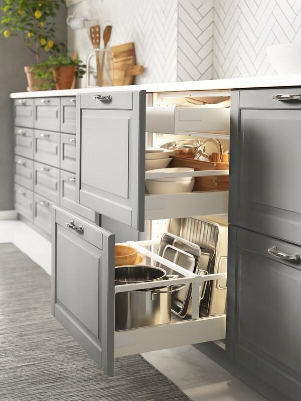 Armarios de base nunha cociña con frontes de caixóns en gris; dous caixóns están abertos e teñen utensilios de cociña e louza no interior.