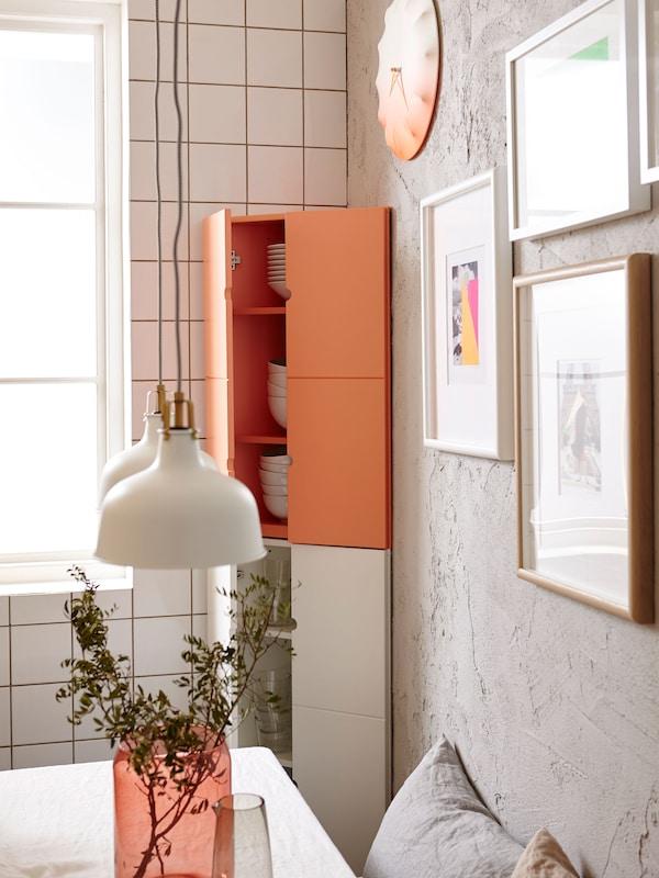 Armarios de esquina IKEA PS en blanco y naranja en una cocina pequeña, con cuadros y reloj en la pared.