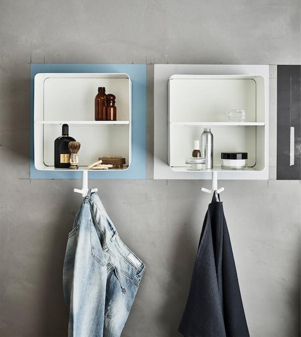 Armarios de pared de distintos colores en un armario con botes y equipo para afeitarse y con una toalla y pantalones.
