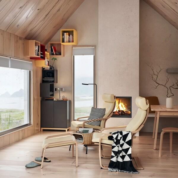Armoire EKET anthracite avec portes à poussoir, dans un séjour avec fauteuils et deux fenêtres.