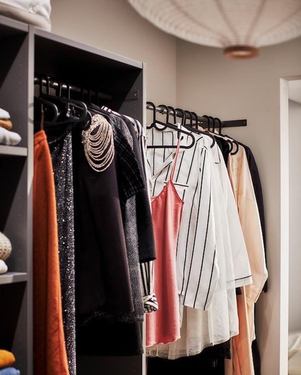 Armoire gris foncé avec des tringles noires où de nombreux vêtements sont suspendus sur de minces cintres noirs.