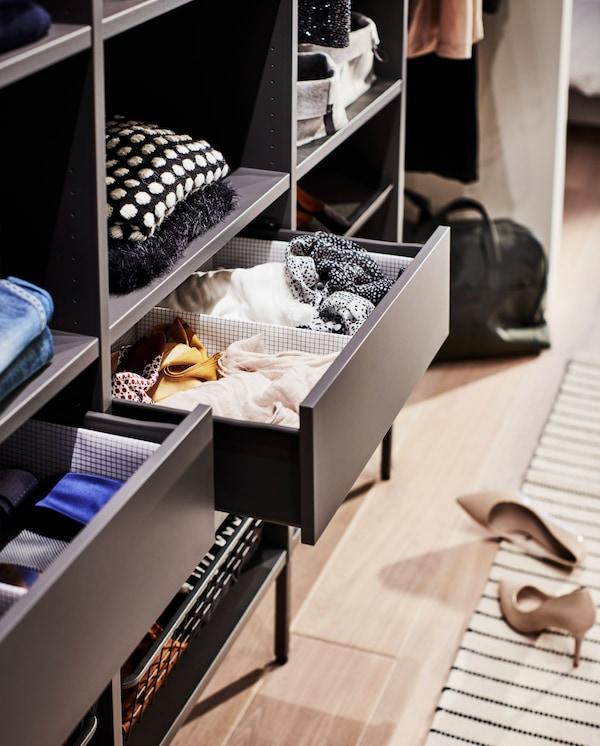 Armoire gris foncé avec deux tiroirs ouverts qui exposent des boîtes à compartiments permettant d'organiser foulards, cravates, etc.