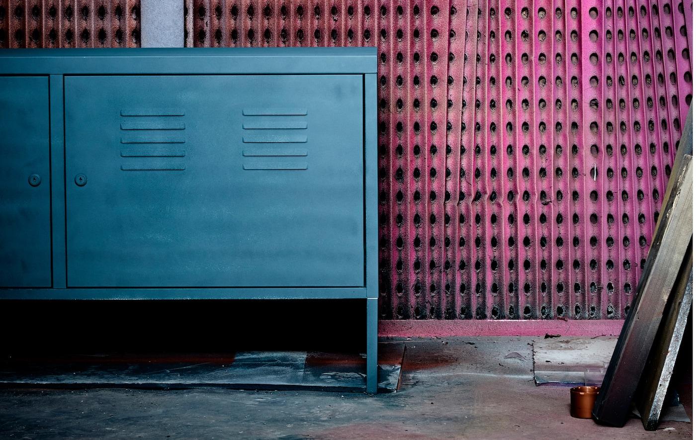 Armoire métallique relookée placée devant un mur graphique.