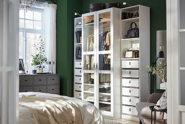 Armoire-penderie blanche à portes vitrées, commode grise et fauteuil gris-beige.