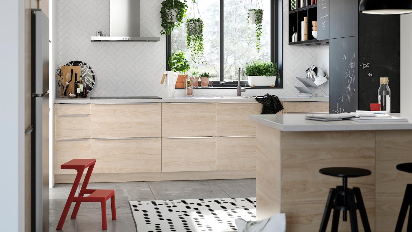 Armoires de cuisine avec portes ASKERSUND à effet frêne clair et armoires avec portes et revêtement anthracite pouvant être utilisées comme tableaux noirs.