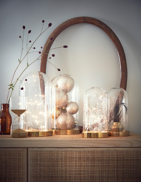 Arrange a delicate, battery powered light chain inside a decorative glass dome, and display it alongside other glass domes filled ornaments.