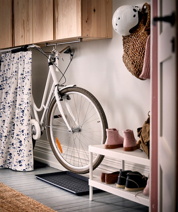 Arranged for accessibility, a bike hung from a rail underneath wall cabinets in a hallway can be hidden by a low curtain.