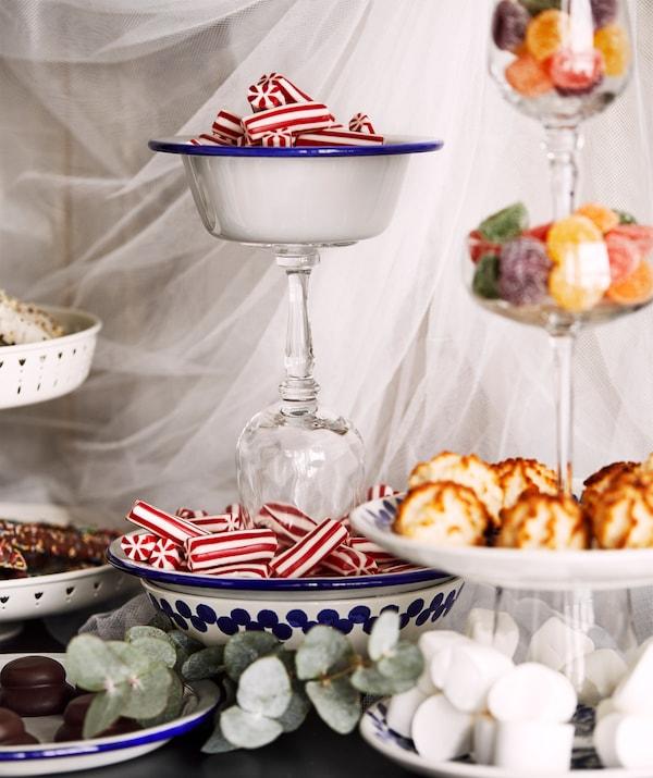 Arrangement festif d'assiettes, de bols, et de verres à vin bien collés les uns sur les autres et présentant des sucreries variées.