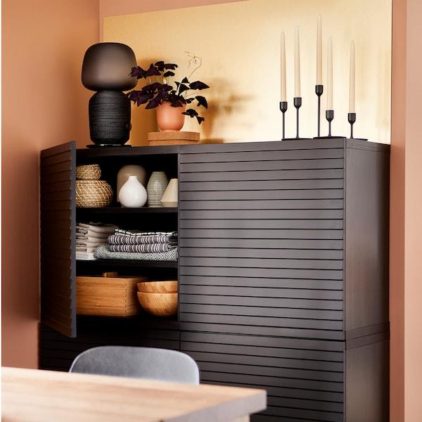 Arrumação com portas em antracite, um painel de parede em cor de bronze, um candeeiro preto, velas e uma planta roxa.