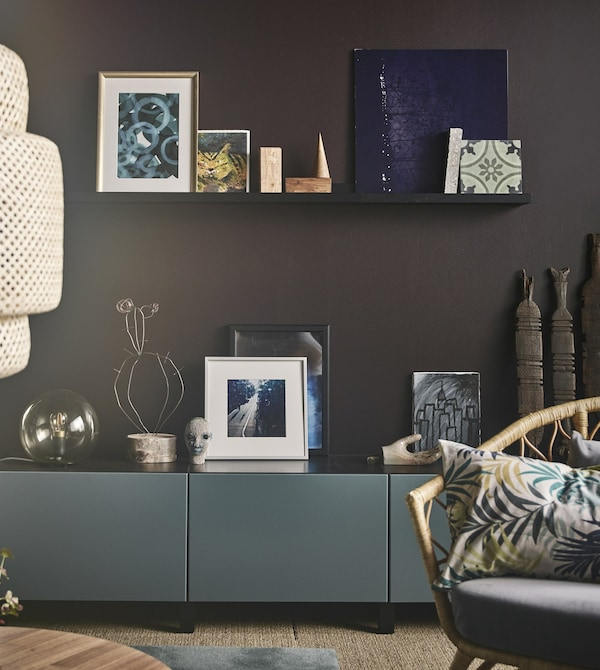 Art arranged on a black picture ledge on a brown wall above a grey-turquoise cabinet in a modern living room.
