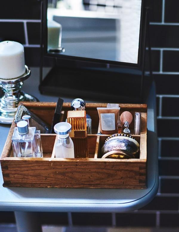Artículos de tocador organizados en una pequeña caja de madera en un cuarto de baño de azulejos negros.