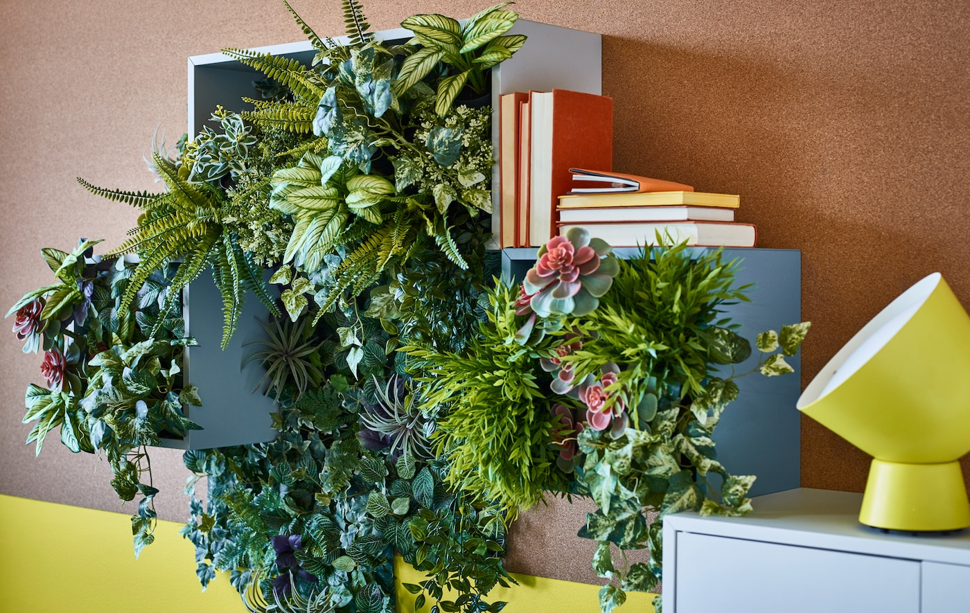 Artificial green potted plants used to create wall décor in open storage boxes.