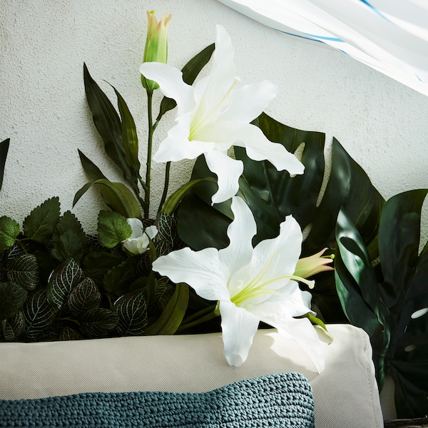 Artificial greenery and flowers cover most of a balcony wall behind a sofa and are shaded by a shower curtain.