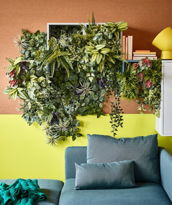Artificial plants cascading out of wall cabinets in a living room area.