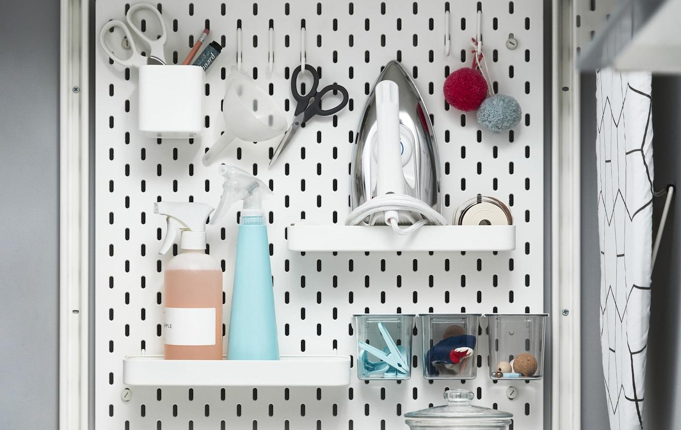 Artigos relacionados com tratamento de roupa arrumados em cima de prateleiras, dentro de vasos e pendurados em ganchos num placar branco.