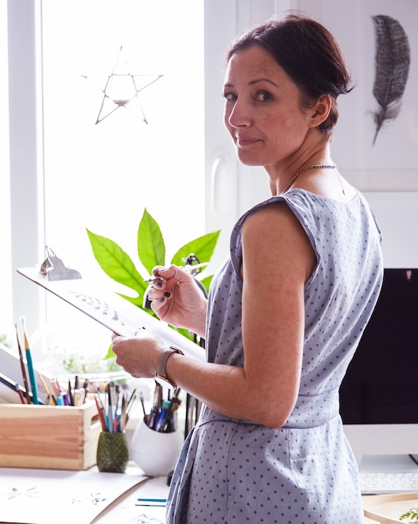 Artist Margo holding a clipboard in her home office/bedroom.
