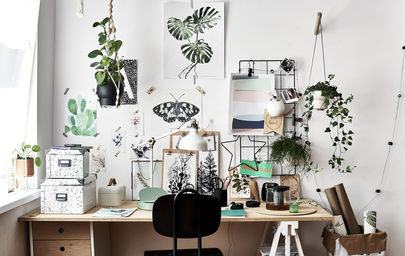 Artwork and inspiration displayed on a wall above a wooden desk and black chair.