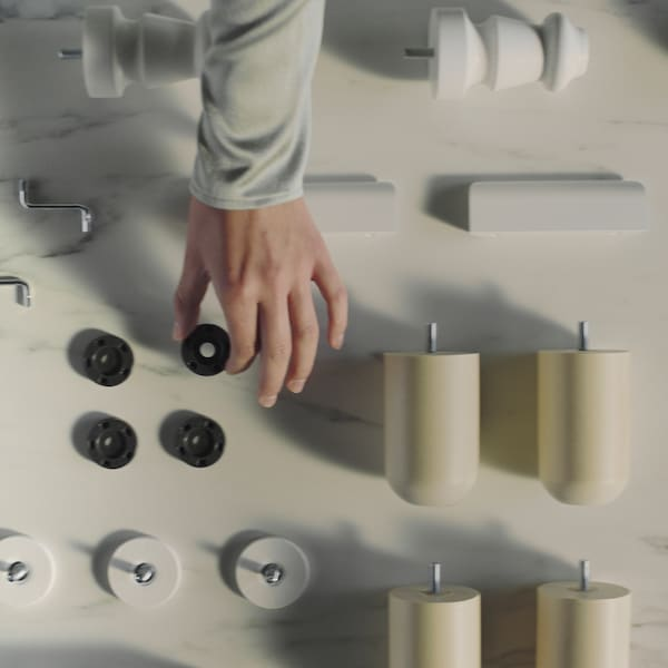 As the camera pans over a neatly arranged display of IKEA spare parts, a hand reaches in and picks one up.