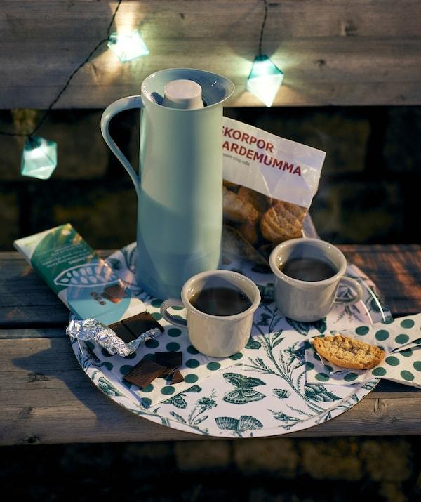 Așezată pe o bancă în oraș, în timpul nopții, pe o tavă MUSTIGHET se află o carafă izotermă BEHÖVD, căni de cafea, fursecuri și ciocolată.