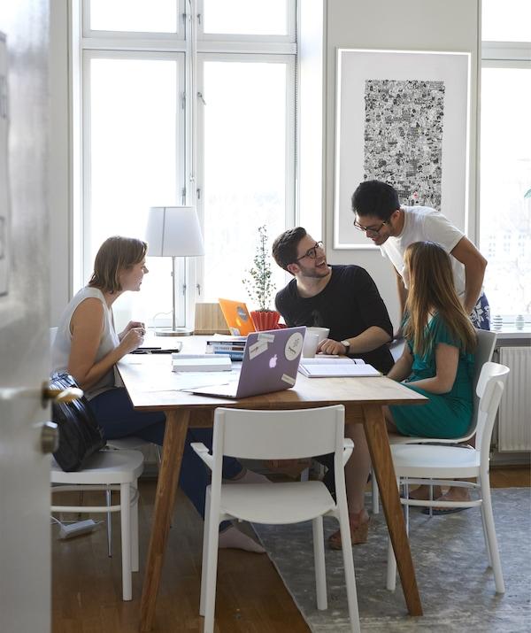 أشخاص مجتمعين حول طاولة مع أجهزة كمبيوتر محمول ودفترية.