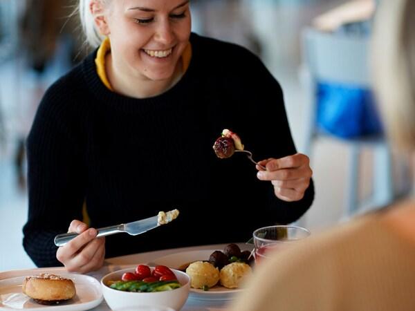 Asiakas syö kasvispyöryköitä IKEA-ravintolassa
