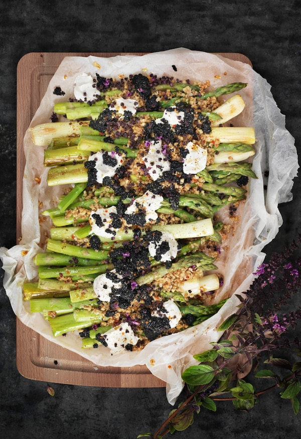 Asparagus salad with seaweed pearls and dollops of crème fraiche served on a wooden chopping board, seen from above.