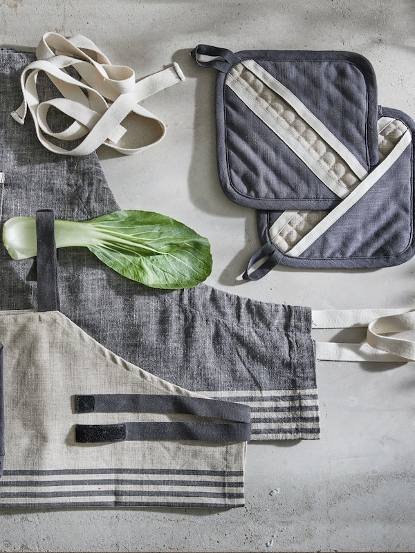 Assortment of grey oven mits and aprons on a brushed grey surface