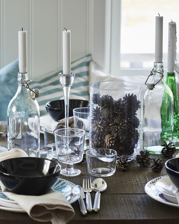 استوحي الإلهام من الطبيعة - تُساعد ظلال الشتاء البارد وأكواز الصنوبر المتناثرة على تهيئة الترتيبات الموسمية المثالية للطاولة.