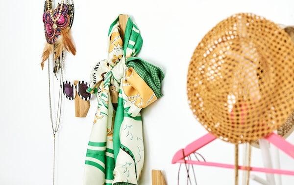 Asymetrické bambusové háčiky na stene, na každom je zavesený iný doplnok – slnečné okuliare, šatka, náhrdelníky a slamený klobúk.