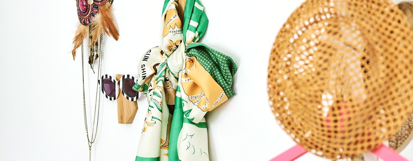 Asymmetrische bamboehaken aan de muur, elk met een ander accessoire, zoals een zonnebril, sjaal, kettingen en een rieten hoed.